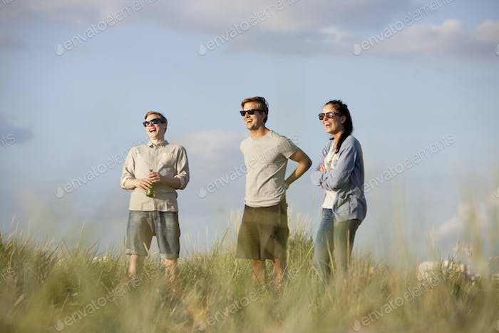 Cheerful friends standing on grassy beach against sky during summer