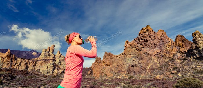 Woman trail runner drinking in inspiring mountains landscape