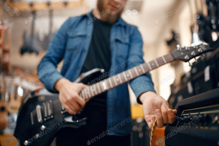 Guitarist plays on electric guitar in music store