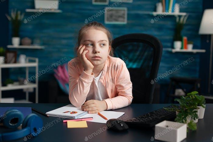 Little girl doing homework feeling bored and sad