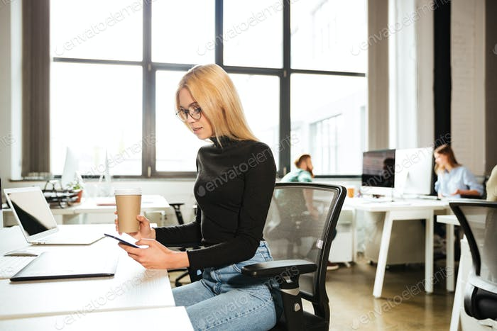 Woman work in office using mobile phone drinking coffee
