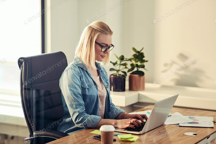 Young businesswoman working online at her desk in an office