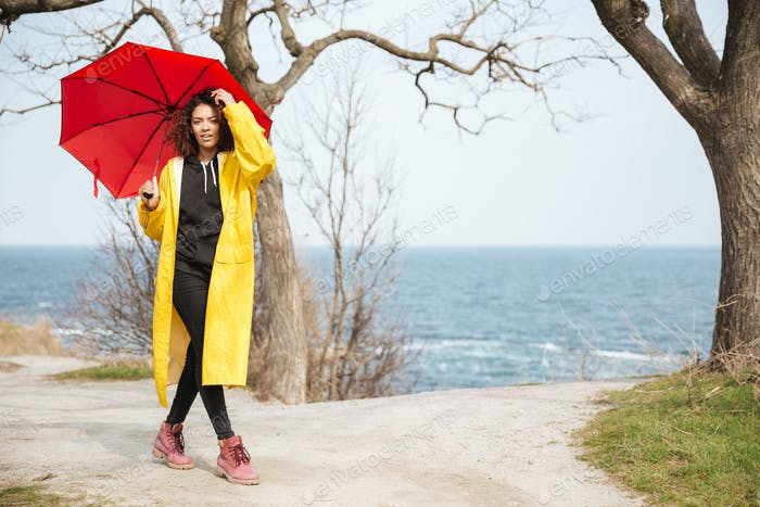 Amazing african curly young lady wearing yellow coat