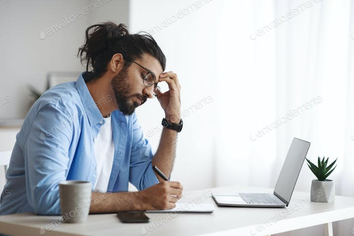 Concentrated Indian Freelancer Guy Noting Ideas To Notepad, Working At Home Office