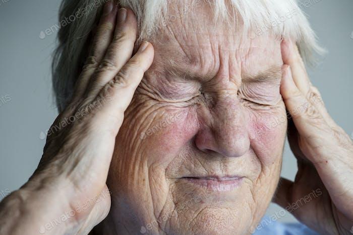 Ältere Frau, die an Migräne leidet