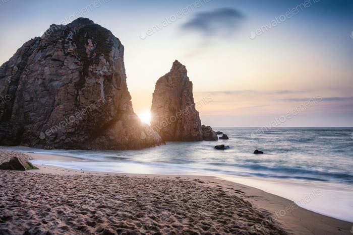 Sunset at Ursa Beach Sea stack, Portugal. Atlantic Ocean Foamy waves rolling to sandy beach. Holiday