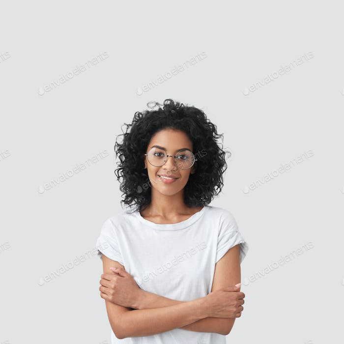 Vertical shot of happy dark skinned female with curly hair, glad to be promoted at work, wears casua