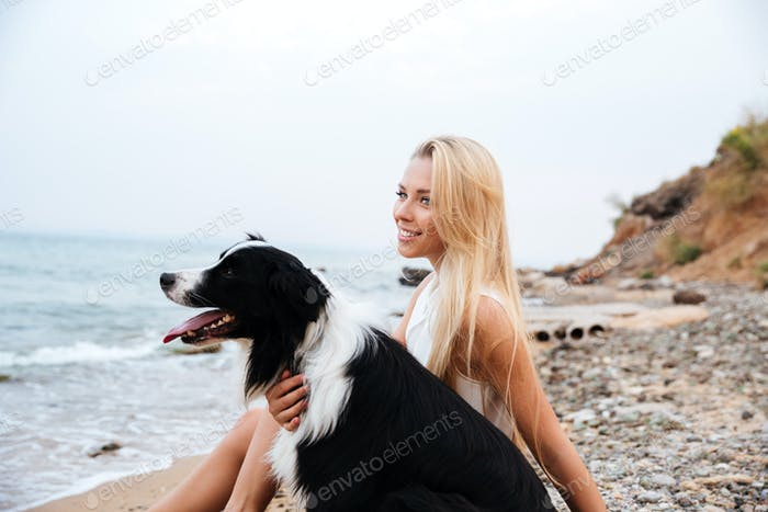 Smiling woman with dog sitting on the beach and thinking