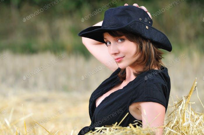 Girl in cowboy hat sits on haystack