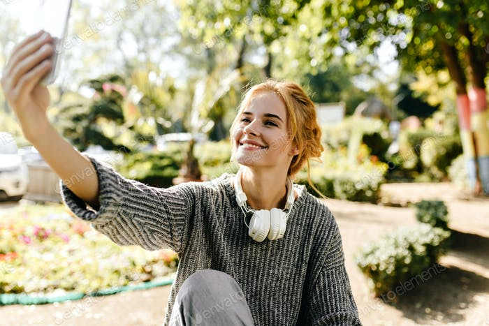 Portrait of european young woman in gray sweater and white headphones in garden. Cute girl with pin