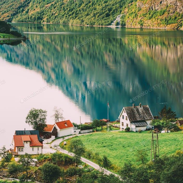 Casas escandinavos en la orilla del fiordo más estrecho en Noruega -