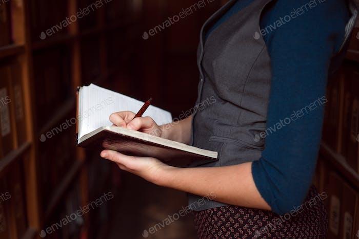Nahaufnahme der weiblichen Hände machen Notizen im Notizbuch