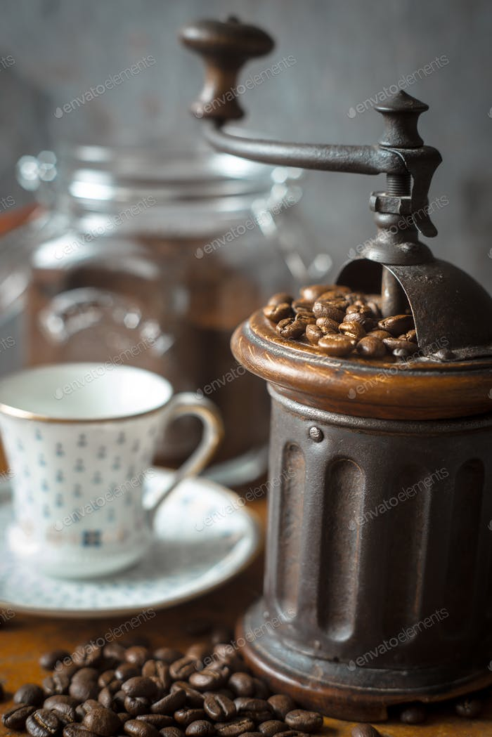 Coffee mill with coffee beans and blurred cup