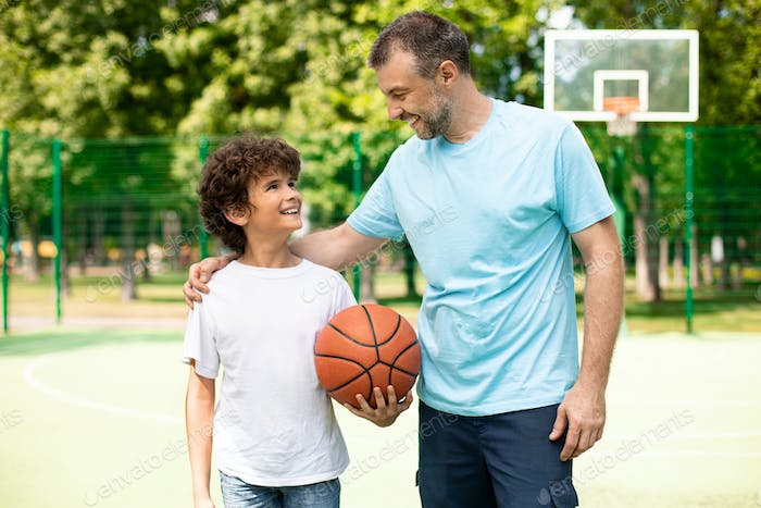 Man posing with son on basketball pitch front view