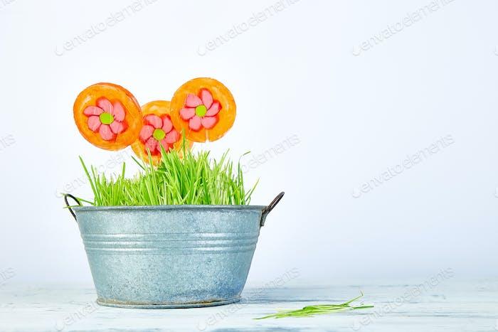 Spring concept. Candy lollipop flower in flowerpot with grass