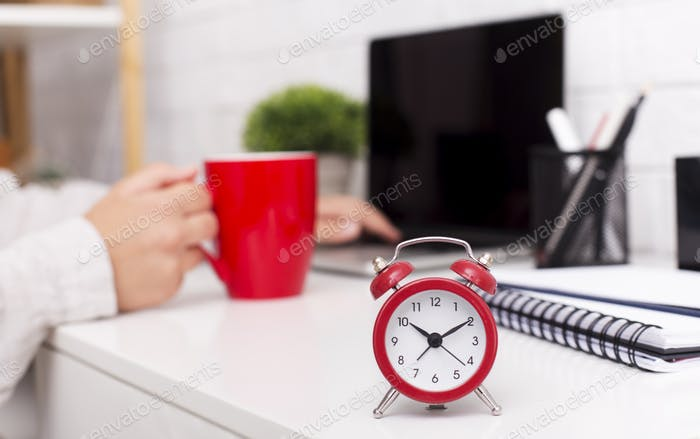 Red alarm clock and morning cup of coffee on office table