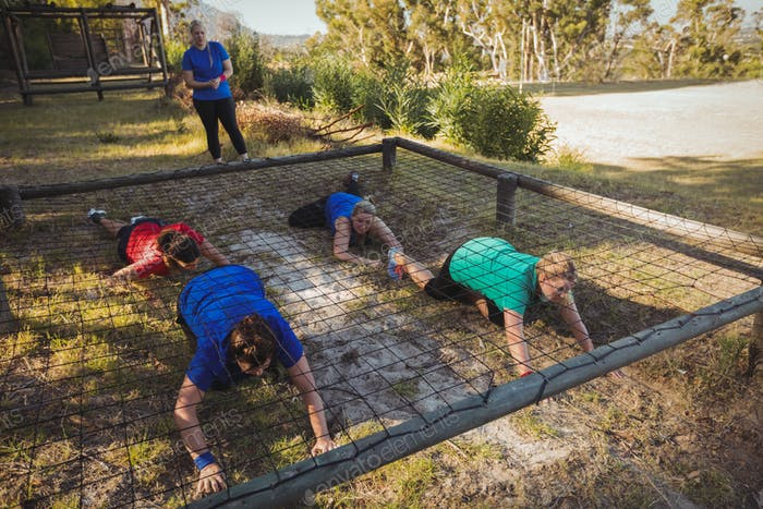 Group of fit women crawling under the net during obstacle course training