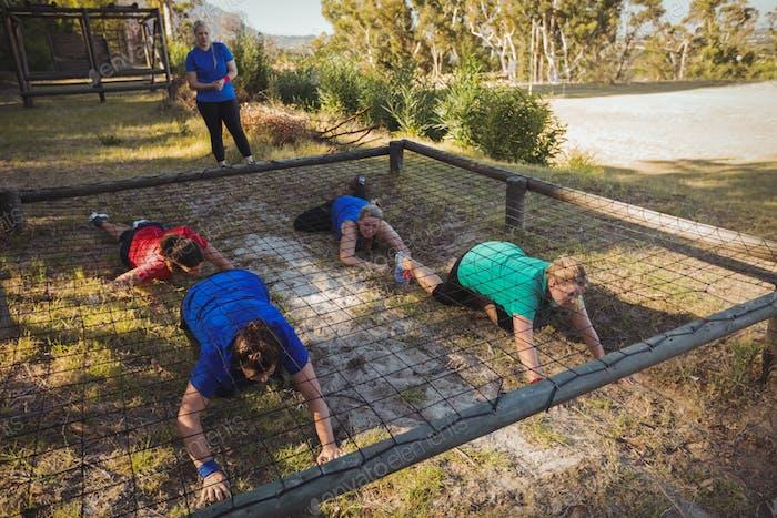 Gruppe von fit Frauen, die während des Trainings im Hinderniskurs unter das Netz kriechen