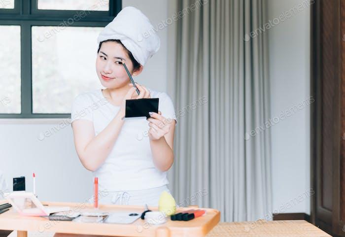 Young Asian woman doing makeup at home