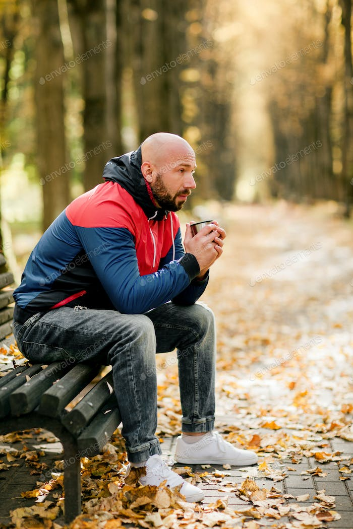 A handsome bearded man is sitting on a bench in an autumn park and drinking hot tea