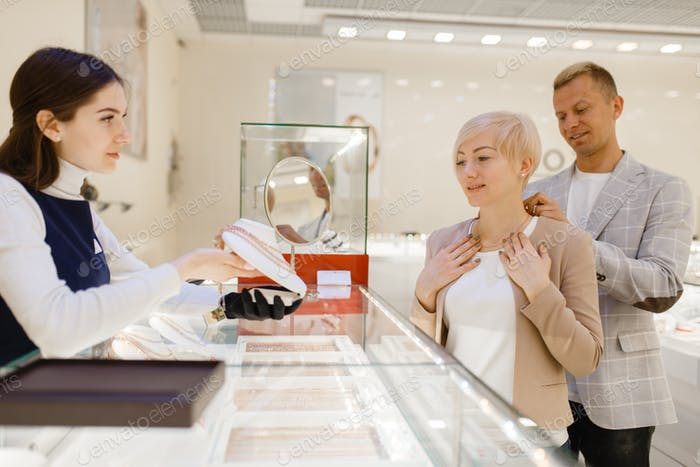 Love couple trying on gold chain in jewelry store
