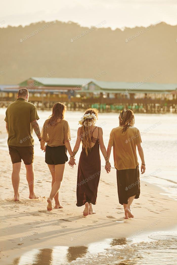 Friends walking on sea beach