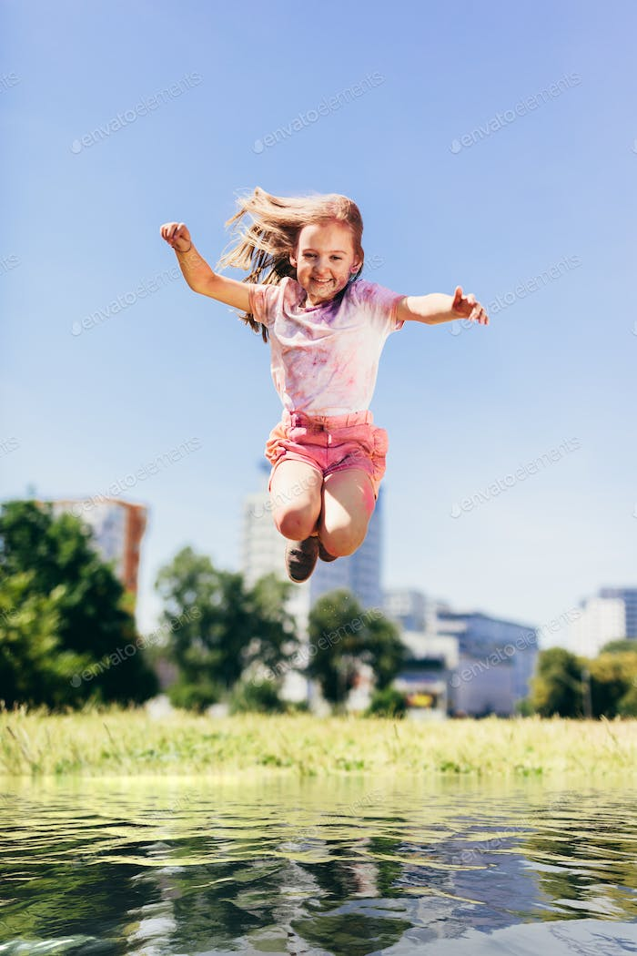 Little girl jumping high above big puddle of water.