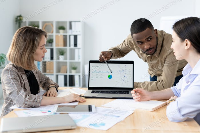 Confident young businessman of African ethnicity looking at one of colleagues
