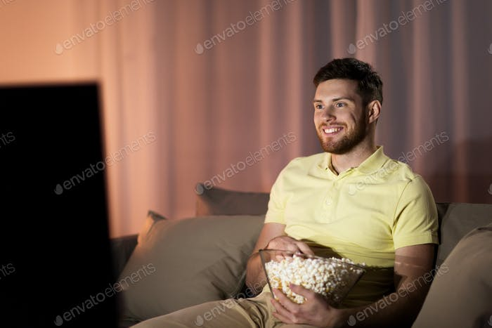 happy man with popcorn watching tv at night