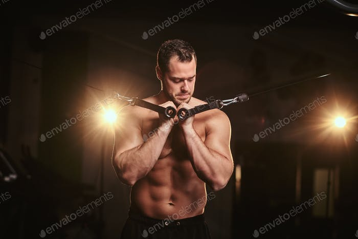Fit sportsman in a dark gym surrounded by smoke