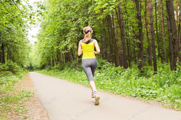 Junge Frau läuft im Freien im Park.