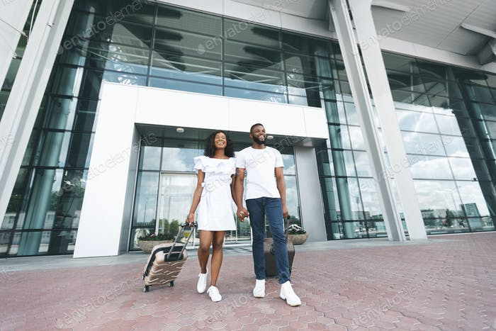Happy millennial black couple enjoying new destination at airport building