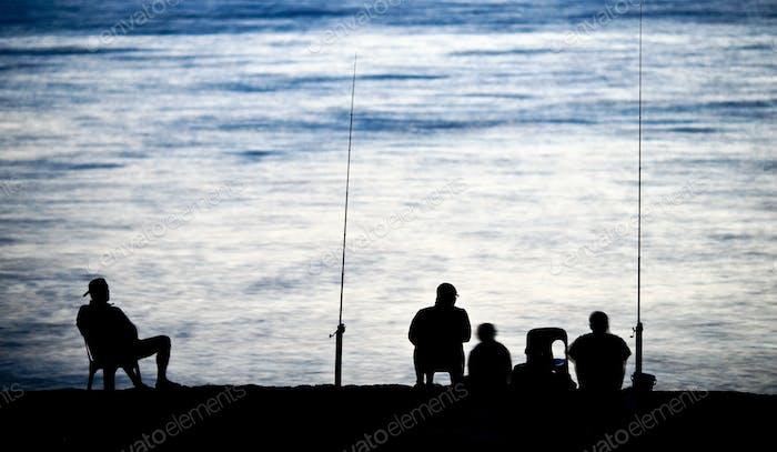 Meer/Ozeanangeln - Fischer sitzen am Meer/Ozean in Dunkelheit