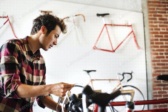 Un hombre en una tienda de bicicletas, leyendo la etiqueta de precio en una bicicleta.