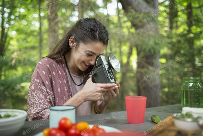 A woman using a vintage camera with separate metal flash unit.