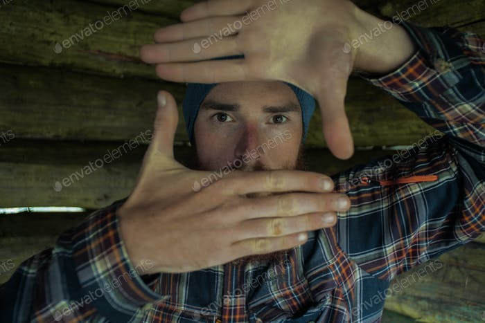 portait of a caucasian male photographer making a composition rectangle sign with his hands