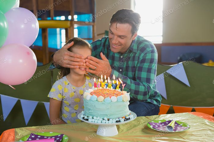 Father closing his daughters eyes during birthday party