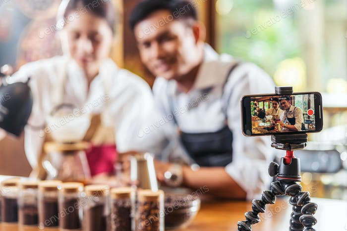 Mobile phone taking Video to two Asian Barista presenting a cup of coffee, dripping coffee