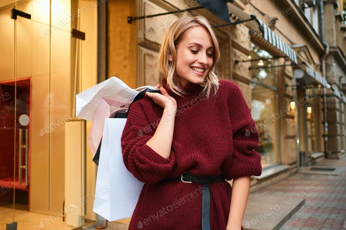 Attractive happy blond girl in knitted sweater with shopping bags after shopping on city street