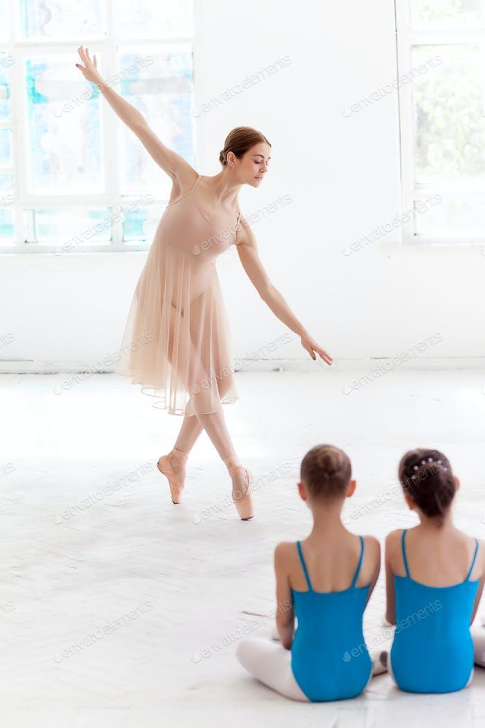 Two little ballerinas dancing with personal ballet teacher in dance studio