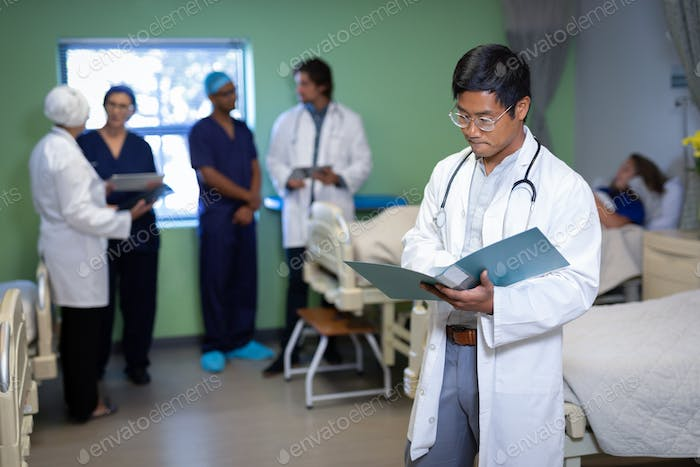 Male doctor looking at medical report in clinic at hospital