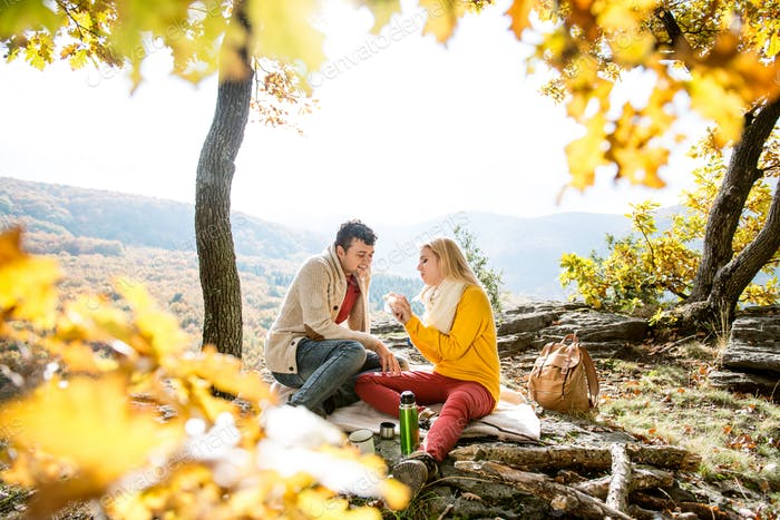 Beautiful couple in autumn forest eating and drinking