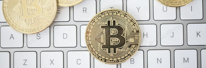 Top view of a golden bitcoin lying on a computer keyboard - a cr