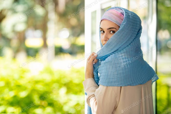 Young attractive Arabian woman in hijab looking at you over her shoulder