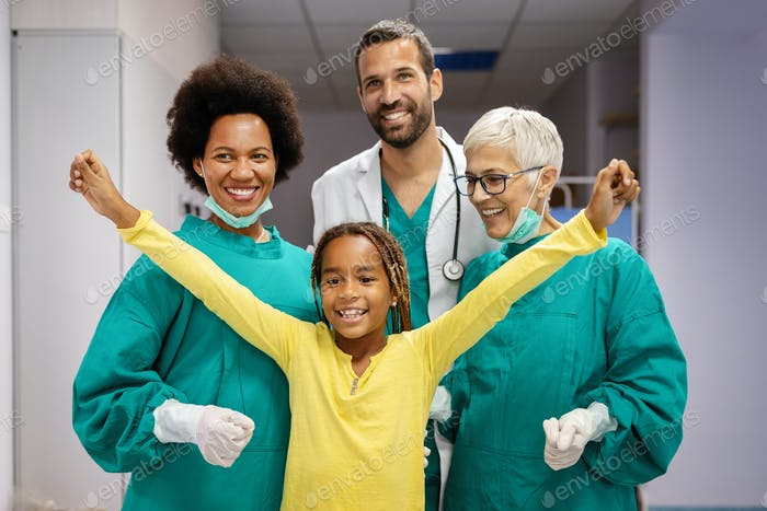 Friendly pediatricians and happy smiling girl patient in hospital