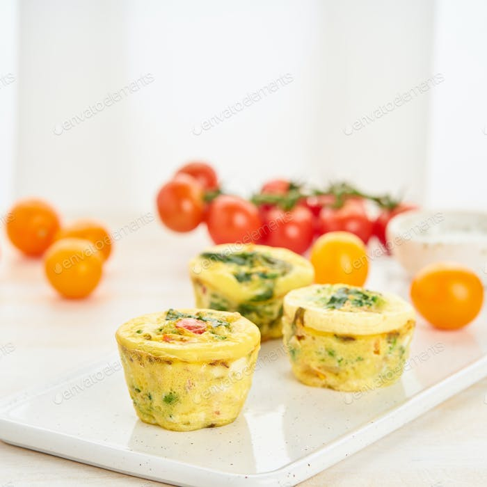 Egg muffins, paleo, keto diet. Omelet with spinach, vegetables, tomatoes baked in small molds