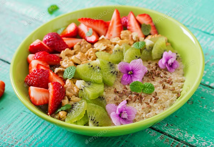 Tasty and healthy oatmeal porridge with berry, nuts and flax seeds