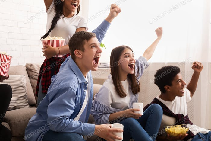 Overjoyed football fans watching match and celebrating victory