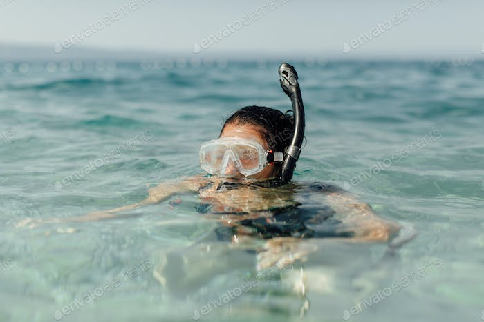 Female swimmer learning to snorkel.
