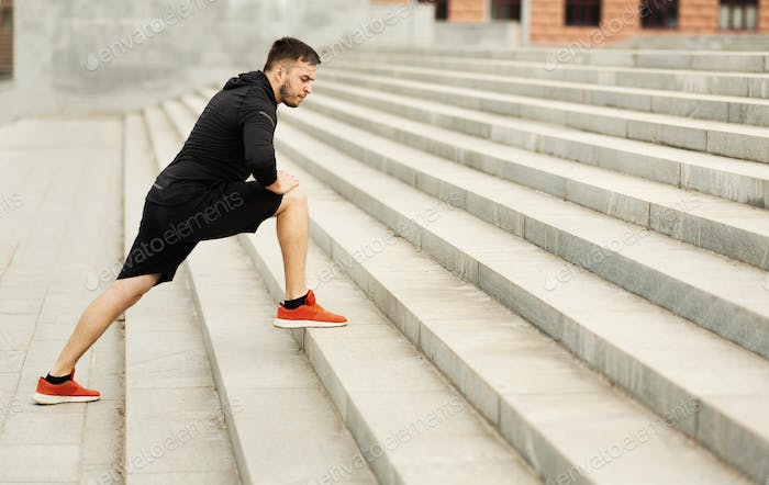 Sportsman stretching legs on gray city steps